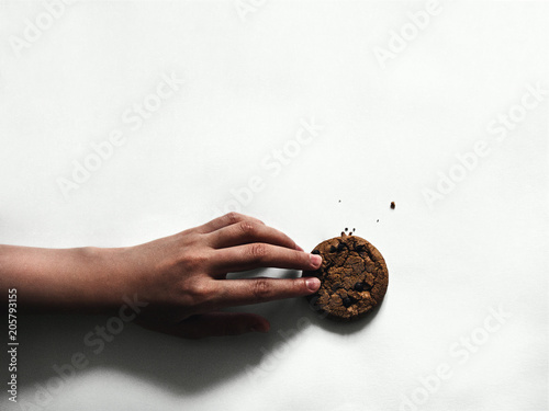 American cookie Top view Girl is holding a cookie with chocolate chips on white background Photo template with copy space