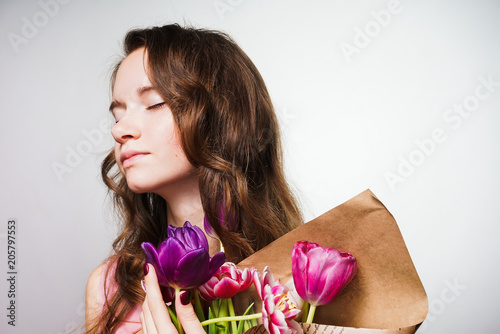 beautiful young woman celebrates mother's day, holds a big bouquet of fragrant flowers