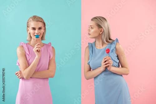 Two girls holding sweets on stick. One looking at another with envy. Isolated on blue and pink background