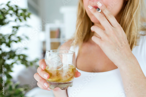 Young woman drinking glass of whiskey and smoking at home.