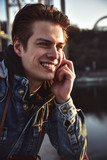 Portrait of happy young man talking on phone in the street.