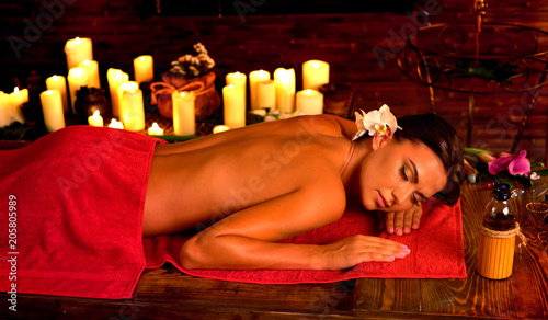 canvas print picture Massage of woman in spa salon. Girl on red towel with light candles background . Luxary interior in oriental therapy salon. Female have relax after sport with bottle oil.