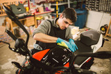 Mechanic polishing and cleaning a motorcycle - 205806331