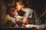 mother puts her daughter to bed and kisses her in   evening