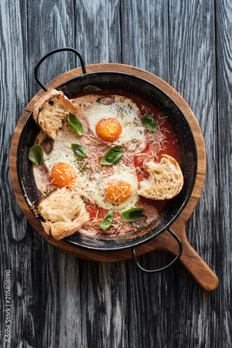 top view of delicious fried eggs with cheese, bread and sauce in pan on wooden cutting board