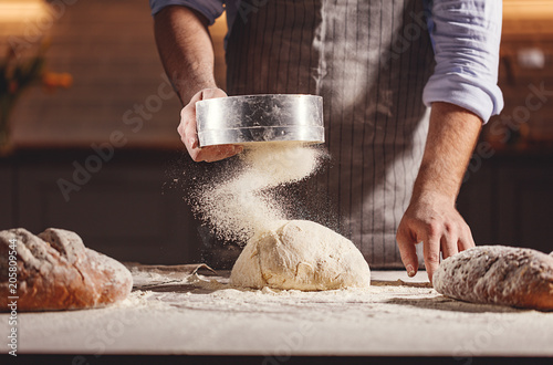 hands of baker's male knead dough