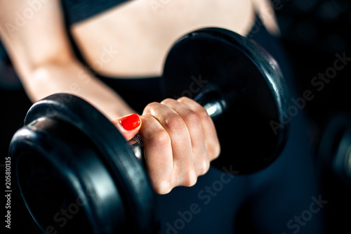 Sticker Girl doing bicep exercise with dumbbells in gym