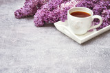 Cup of tea on white tray with lilac border on gray background. Copy space - 205812758