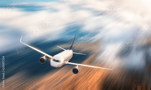 Modern airplane with motion blur effect is flying over low clouds at sunset. Passenger airplane, blurred clouds, forest, sunlight in dusk. Passenger aircraft. Business travel. Commercial plane.Concept