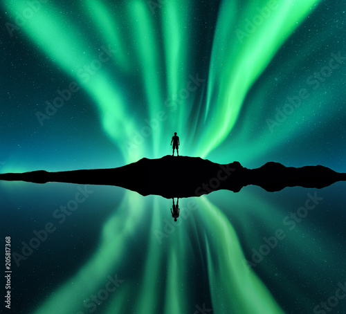 Fotobehang Noorderlicht Aurora borealis and silhouette of standing man. Lofoten islands, Norway. Aurora and happy man. Stars and green polar lights. Night landscape with aurora, man, lake, sky reflection in water. Travel