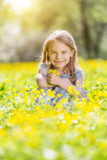 Happy little girl on spring blooming meadow - 205823911