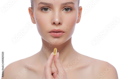Beautiful young woman holding fish oil pill in your hand. Healthy eating concept.