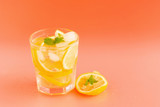 Detox Water with lemon in a glass on an orange background