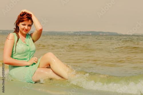 Foto Murales Redhead woman posing in water during summertime