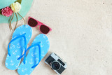 Beach background.  Top view of beach sand with straw hat, sunglasses, slippers and camera.  Summer background concept.