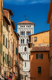 View of Lucca historic center with Saint Michael in Foro medieval bell tower seen from city narrow street