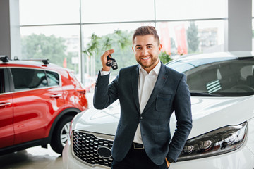 Man is holding a key of their new car, looking at camera and smiling.