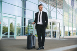 Confident mature businessman standing outside the airport - 205856134