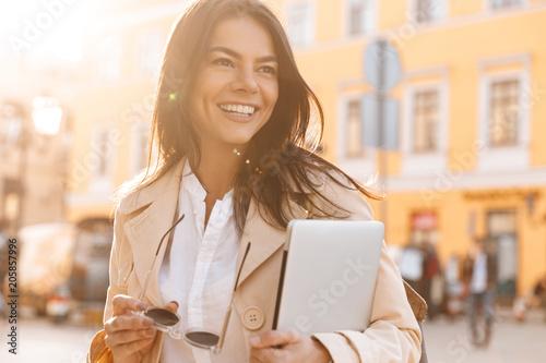 Szczęśliwa brunetki kobieta w kurtki mienia laptopie