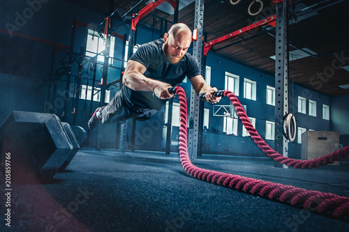 Sticker Men with battle rope battle ropes exercise in the fitness gym.