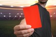 Referee is showing red card as a penalty for a foul in soccer stadium.
