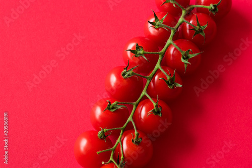 Foto Murales cherry-tomatoes-on-red-background-with-room-for-text