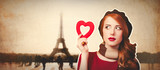 Redhead girl with shape heart and Eiffel tower on background