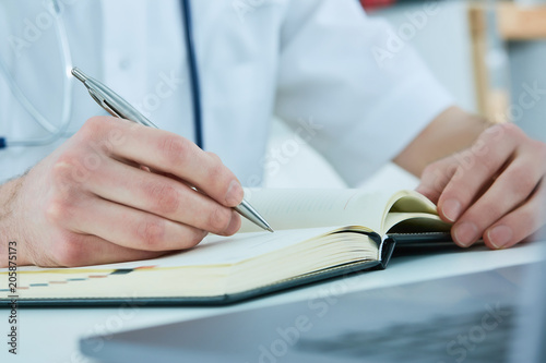 Male doctor or medical student holding ballpoint pen and writing on notepad. Therapist fills the patient admission schedule