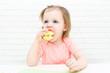 Cute little 2 years girl eats apple