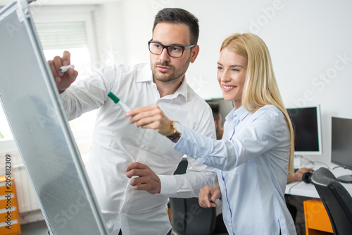 Beautiful business woman and man working with flipchart in office