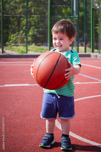 Fotobehang Basketbal a boy of two years playing with a ball on the basketball court. Toddler boy playing basketball