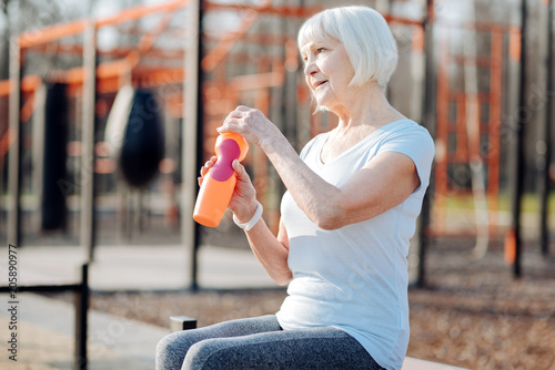 Relaxation. Content blond woman holding a bottle of juice and relaxing while exercising