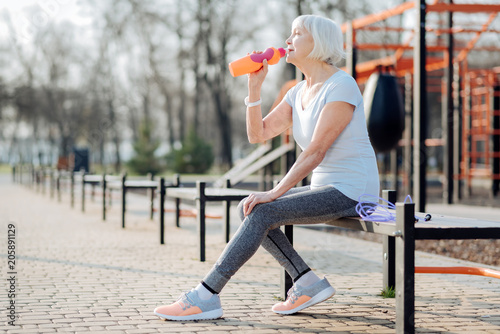 I love juice. Content slim woman holding a bottle of juice and relaxing while exercising