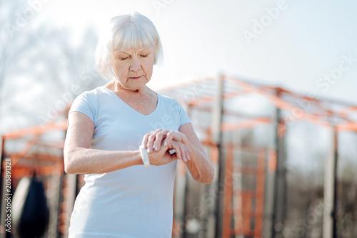 Świetny zegarek. Zdecydowana stara kobieta patrzeje jej sprawność fizyczna tropiciela podczas gdy ćwiczący w na wolnym powietrzu
