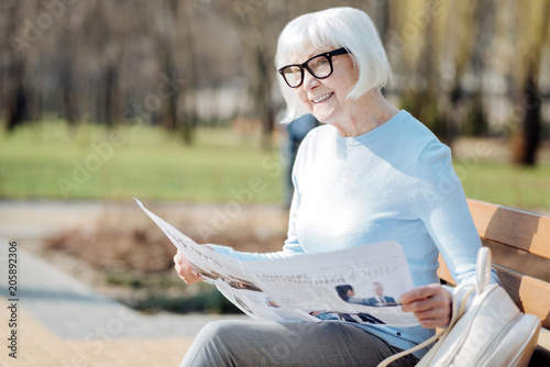 Great news. Content aged woman reading a newspaper while sitting on the bench