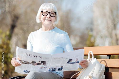 Wonderful news. Alert aged woman reading a newspaper while sitting on the bench