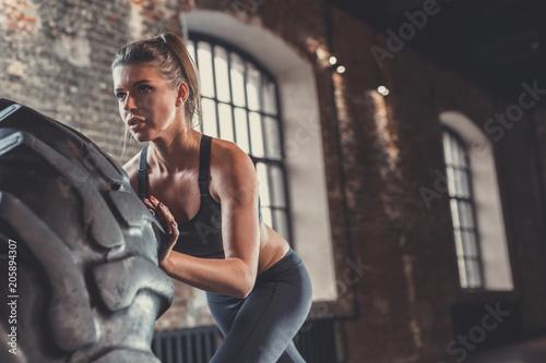 Młoda sportowa kobieta z kołem w loft