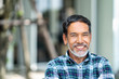 Leinwandbild Motiv Portrait of happy mature man with white, grey stylish short beard looking at camera outdoor. Casual lifestyle of retired hispanic people or adult asian man smile with confident at coffee shop cafe.