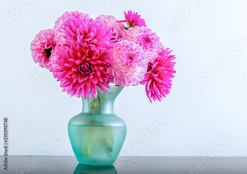 A mixture of pink dahlias in a turquoise vase.