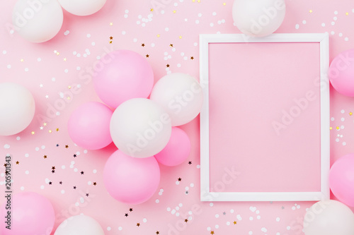 Birthday mockup with frame, pastel balloons and confetti on pink table top view. Flat lay composition.