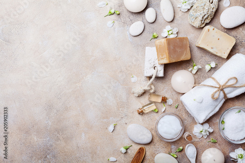 Spa setting from body care and beauty products with flowers on stone background top view. Flat lay.