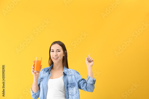Young woman with glass of orange juice on color background