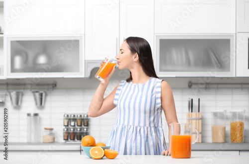 Leinwanddruck Bild Young woman drinking orange juice in kitchen