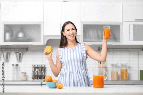 Young woman with glass of orange juice in kitchen
