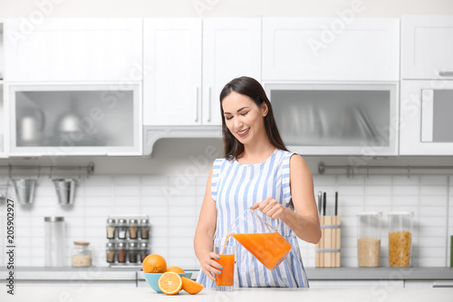 Young woman pouring orange juice into glass in kitchen
