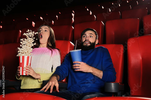 Emotional young couple watching movie in cinema