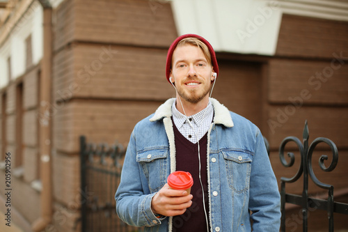 Portrait of hipster with earphones listening to music and drinking coffee outdoors