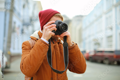 Portrait of hipster taking photo outdoors