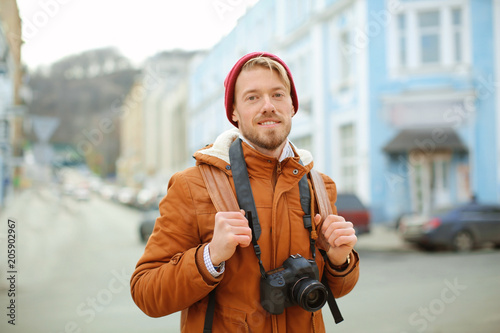 Portrait of hipster with camera outdoors