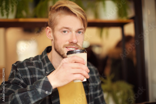 Portrait of trendy hipster drinking coffee in cafe